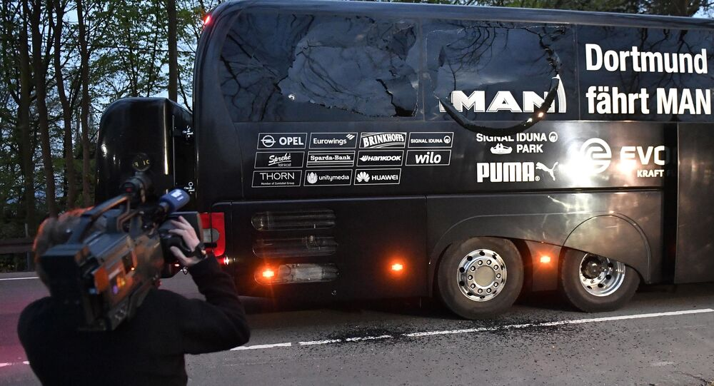 A camera man films Dortmund's team bus after it was damaged in an explosion before the Champions League quarterfinal soccer match between Borussia Dortmund and AS Monaco in Dortmund, western Germany, Tuesday, April 11, 2017.