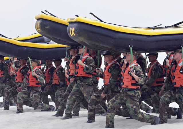 Navy SEAL trainees carry inflatable boats at the Naval Amphibious Base Coronado in Coronado, Calif. In a highly unusual move, the training death of an aspiring Navy SEAL, 21-year-old Seaman James Derek Lovelace, has been ruled a homicide by the San Diego County Medical Examiner
