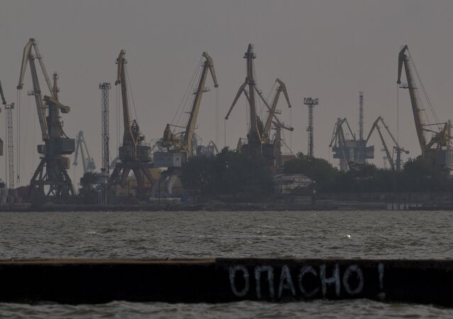 A man jumps in the Sea of Azov, backdropped by cranes of the commercial port, at dusk in Mariupol, Ukraine, Sunday, May 18, 2014