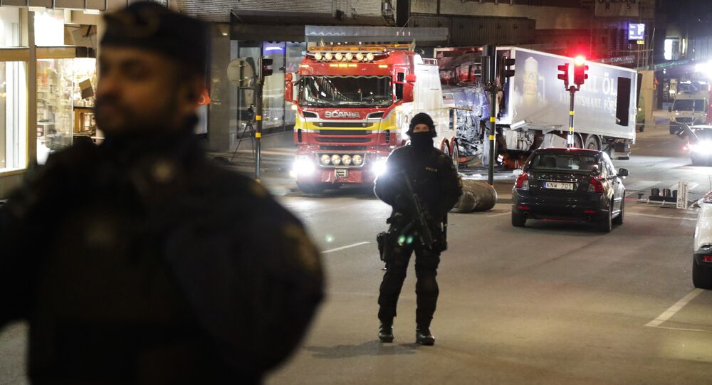 Police officers guard the scene as a truck is pulled away by a service car after it was driven into a department store in Stockholm, Sweden, Saturday, April 8, 2017
