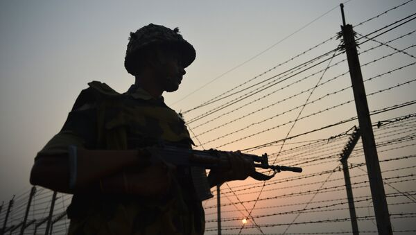An Indian Border Security Force (BSF) soldier patrols along a fence at the India-Pakistan border in R.S Pora, southwest of Jammu, on October 3, 2016 - Sputnik International