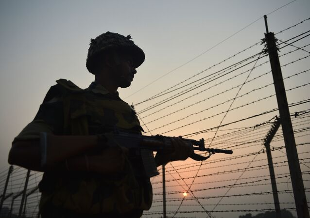 An Indian Border Security Force (BSF) soldier patrols along a fence at the India-Pakistan border in R.S Pora, southwest of Jammu, on October 3, 2016