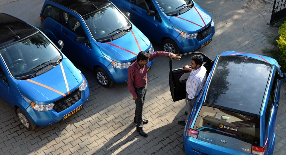 An employee of Indian company Carzonrent interacts with a prospective customer ahead of hiring a Mahindra Reva electric car in Bangalore