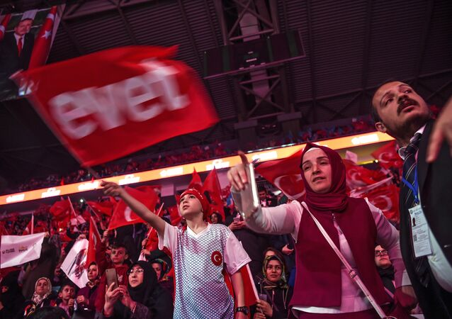 Supporters wave Turkey's national flags and a flag reading Yes in Turkish (L) during a campaign rally of Turkey's president on April 12, 2017 during a 15 July Martyrs meeting and a campaign rally for the yes vote in a constitutional referendum in Istanbul