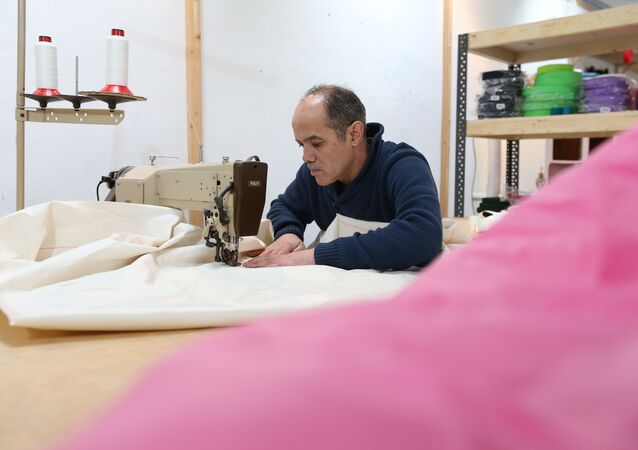 Syrian refugee Mohammed Alsahani used to make curtains in Damascus and now works with the sailmaker Coastworxx near the port of Kiel in Germany.
