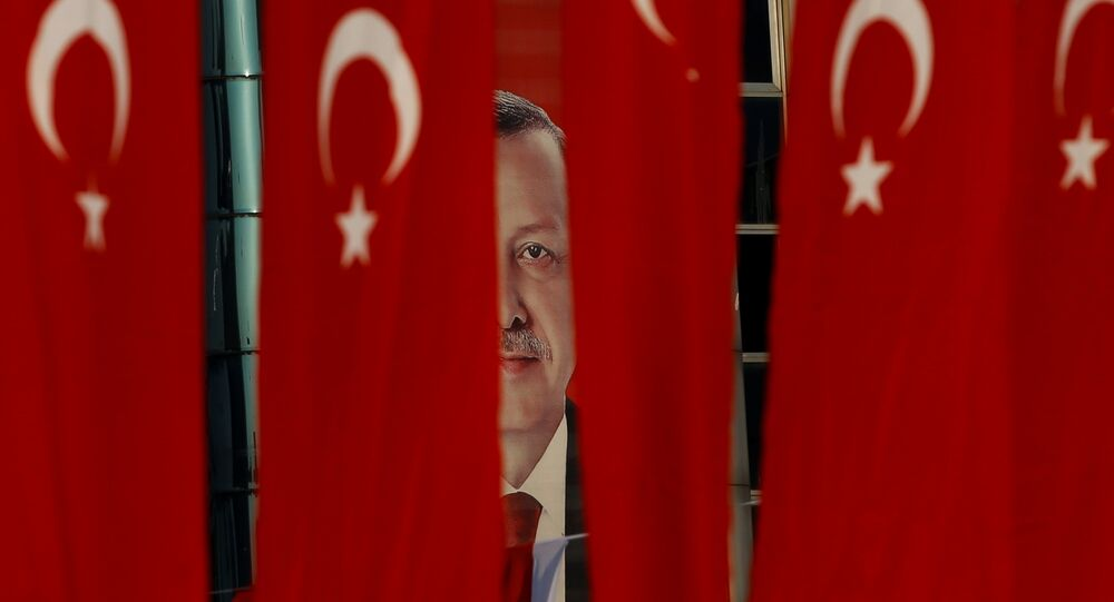 A picture of Turkish President Tayyip Erdogan is seen through Turkish national flags ahead of the constitutional referendum in Istanbul, Turkey, April 14, 2017.