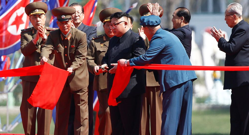 North Korean leader Kim Jong Un cuts the ribbon during an opening ceremony of a newly constructed residential complex in Ryomyong street in Pyongyang, North Korea April 13, 2017.