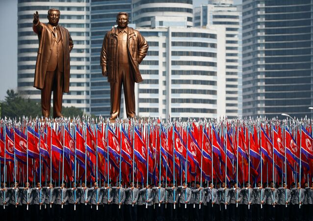 People carry flags in front of statues of North Korea founder Kim Il Sung (L) and late leader Kim Jong Il during a military parade marking the 105th birth anniversary Kim Il Sung, in Pyongyang April 15, 2017.