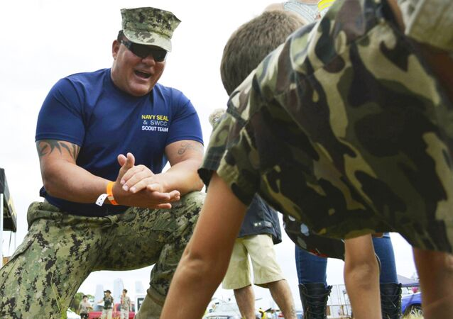 Chief Petty Officer Joseph Schmidt III, assigned to the Navy SEAL and SWCC Scout Team, encouraging a young fan to do pushups at the 2016 Stuart Air Show in Stuart, Fla.