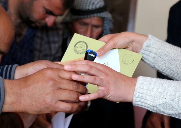 People hold ballot papers at a polling station during a referendum in the Kurdish-dominated southeastern city of Diyarbakir, Turkey