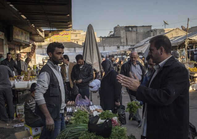 A man talks to a seller at a Damascus market. File photo