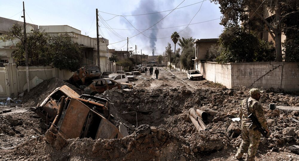 An Iraqi forces member stands next to a crater made by an air strike in west Mosul as Iraqi troops continue battling against Islamic State (IS) group fighters to further advance inside the city, on March 7, 2017