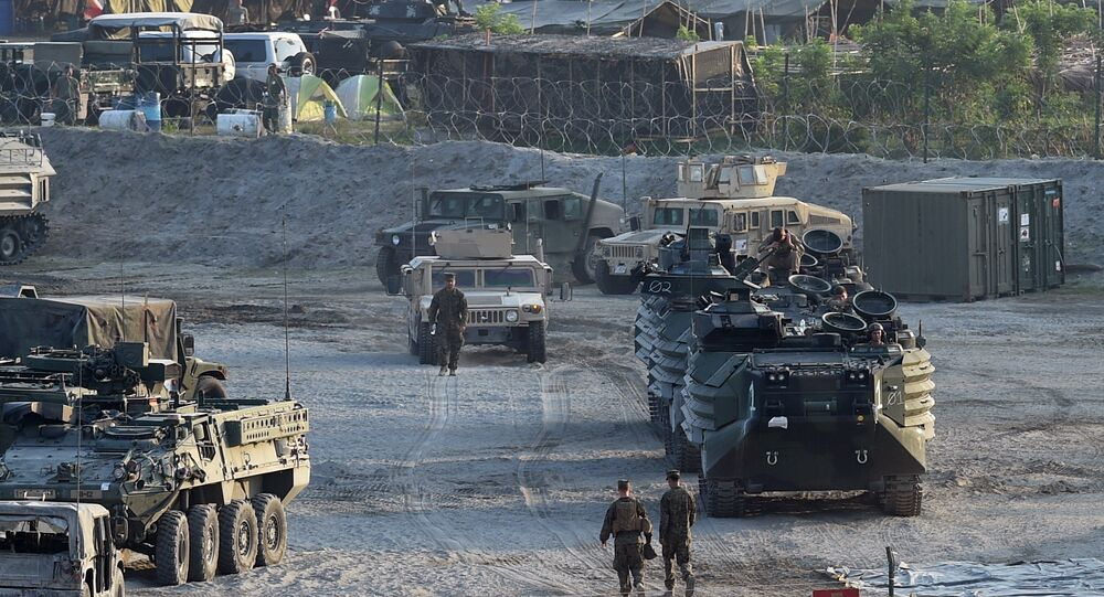 This file photo taken on April 14, 2016 shows US marines walking next to their transport and amphibious vehicles at a temporary camp for the Balikatan joint US-Philippine military exercise at Crow Valley, in Capas town, north of Manila