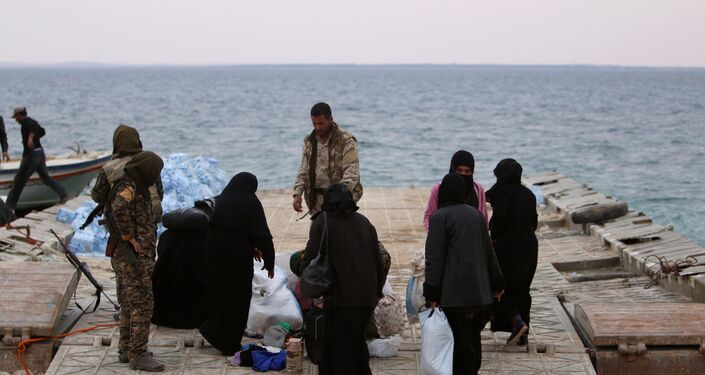 Syrian Democratic Forces (SDF) fighters relocate people that fled from Raqqa city on the bank of the Euphrates river, west of Raqqa city, Syria April 8, 2017
