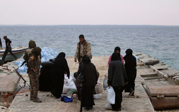 Syrian Democratic Forces (SDF) fighters relocate people that fled from Raqqa city on the bank of the Euphrates river, west of Raqqa city, Syria April 8, 2017 - Sputnik International