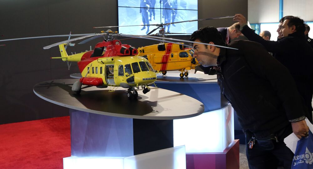 An Iranian man looks at model of a helicopter at the stand of the Russian company Rostec on December 22, 2015 during the Russia National Industrial Exhibition in Tehran