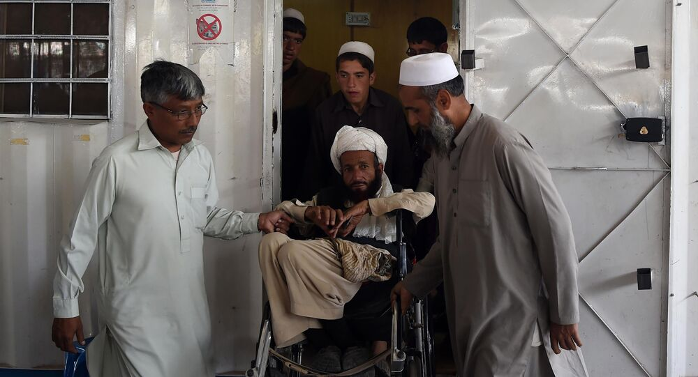 Afghan refugees help a disabled refugee at the United Nations High Commissioner for Refugees (UNHCR) repatriation centre on the outskirts of Peshawar on April 11, 2017, as they prepare to return to their home country after fleeing civil war and Taliban rule