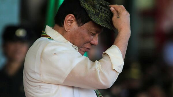 Philippine President Rodrigo Duterte tries on a military hat given to him during the 120th founding anniversary of the Philippine Army (PA) at Taguig city, metro Manila, Philippines, 4 April 2017 - Sputnik International