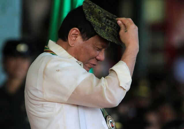 Philippine President Rodrigo Duterte tries on a military hat given to him during the 120th founding anniversary of the Philippine Army (PA) at Taguig city, metro Manila, Philippines April 4, 2017