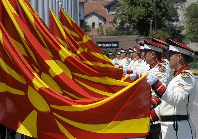 Macedonian Army honor guard officers change the national flags during a special ceremony in front of the government building in Macedonia's capital Skopje, Friday, Aug. 9, 2013