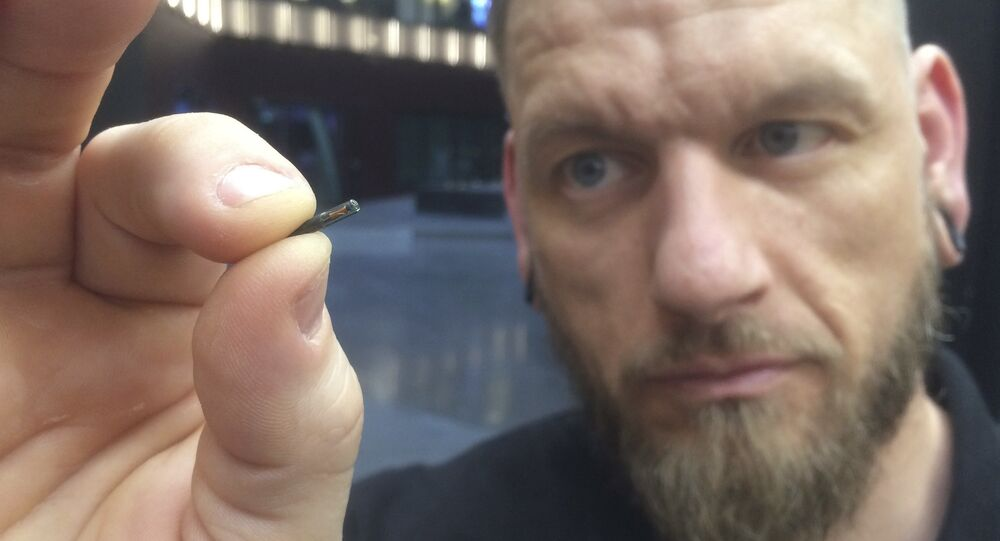 "Self-described ""body hacker"" Jowan Osterlund from Biohax Sweden, holds a small microchip implant, similar to those implanted into workers at the Epicenter digital innovation business centre during a party at the co-working space in central Stockholm, Tuesday March 14, 2017"