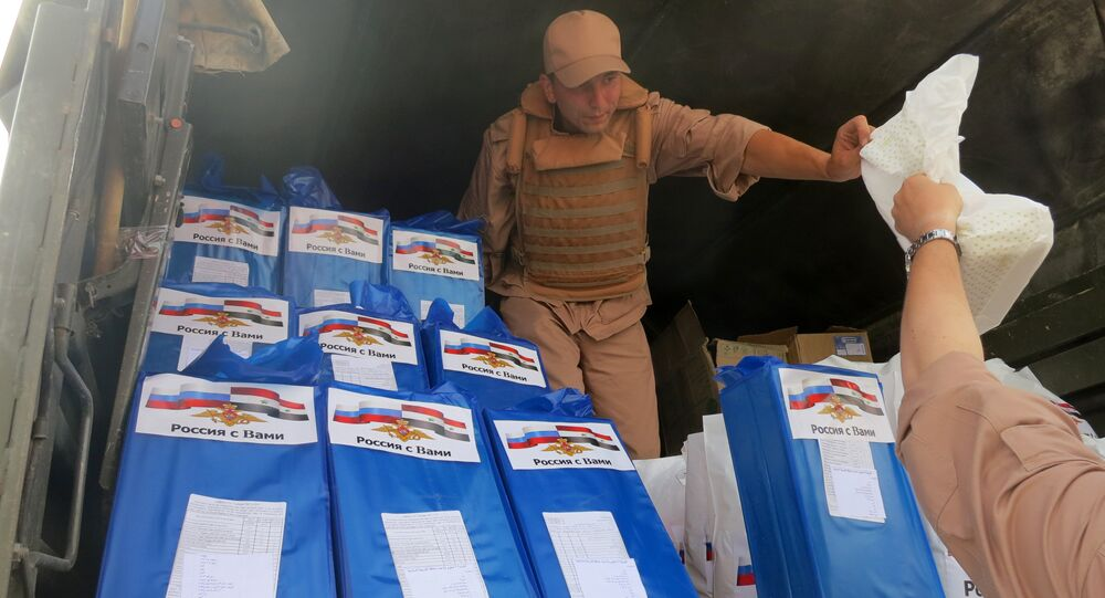 (File) A picture taken during a press tour organized by the Russian Army shows a Russian soldier distributing food parcels on April 8, 2016 in al-Qaryatain, a town in the province of Homs in central Syria, a few days after Syrian regime forces seized it from jihadists of the Islamic State (IS) group