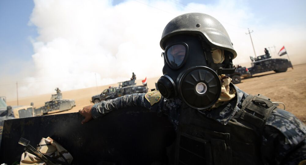 Iraqi forces wear gas masks for protection as smoke billows in the background after Islamic State (IS) group jihadists torched Mishraq sulphur factory, near the Qayyarah base, about 30 kilometres south of Mosul, during an operation to retake the main hub city from IS on October 22, 2016