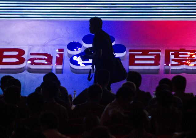 FILE - In this Sept. 2, 2011 file photo, a photographer walks past the logo of Baidu Inc., which operates China's dominant search engine, during a technology innovation conference held by the company at China's National Convention Center in Beijing, China. China issued new regulations on Saturday, June 25, 2016 demanding search engines clearly identify paid search results, months after a terminally-ill cancer patient complained that he was misled by the giant search engine Baidu.