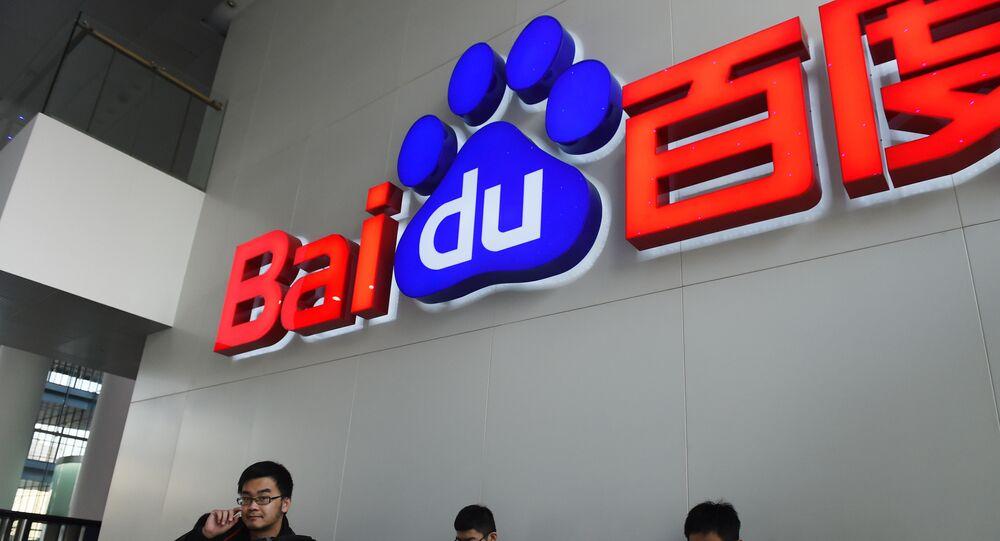People sit below a Baidu logo at the Baidu headquarters in Beijing on December 17, 2014.