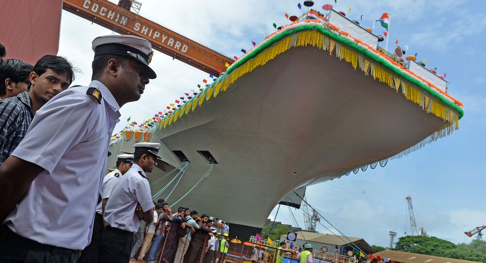 Indian naval officers stand guard during the launch of the indigenously-built aircraft carrier INS Vikrant at the Cochin Shipyard in Kochi on August 12, 2013