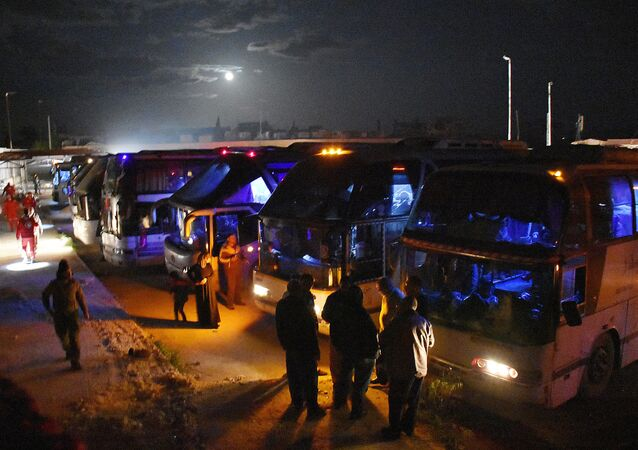 Syrian militants and members of their families from Madaya and Zabadani board buses heading to Ramousseh crossing, in Aleppo, on April 14, 2017, as part of a deal between the opposition and the Syrian government