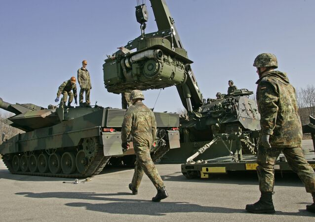The crew of a 'Buffalo' wrecker tank, right, of the German Army lifts the engine of a Leopard 2 battle tank, left, for repair during a demonstration at the Bayern Barracks in Munich, southern Germany, on Wednesday, Feb. 20, 2008