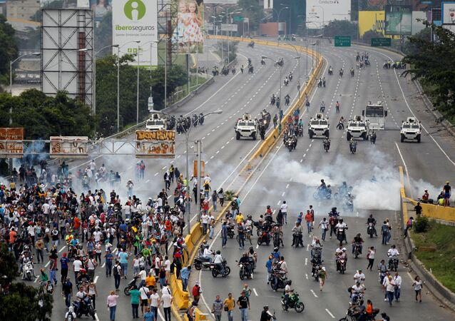Demonstrators run away from tear gas during clashes with police while rallying against Venezuela's President Nicolas Maduro in Caracas, Venezuela, April 20, 2017.