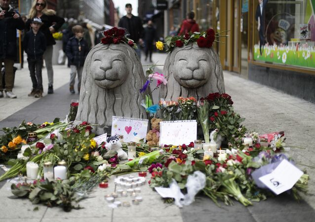 Flowers and candles are placed around stone lions near the department store Ahlens following a suspected terror attack in central Stockholm, Sweden, Saturday, April 8, 2017.