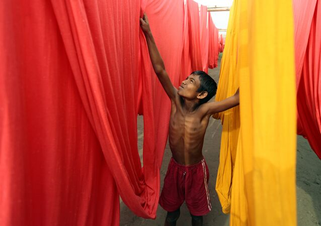 In this Saturday, Dec. 22, 2012 file photo, a Bangladeshi child works at a clothes-dyeing factory in Narayanganj, outskirts of Dhaka, Bangladesh.