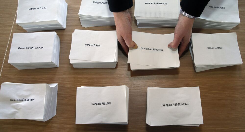 A worker places the ballots on a table at a polling station at the town hall of Saint Jean le Vieux, southwestern France, Friday, April 21, 2017.