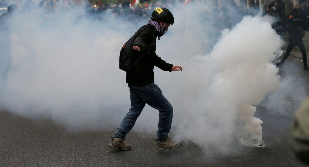 A protester kicks back a tear gas grenade during a demonstration for a social first round on the eve of the first round in the French presidential election, in Paris, France