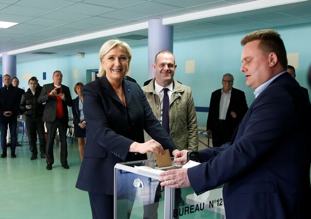 Marine Le Pen (L), French National Front (FN) political party leader and candidate for French 2017 presidential election, casts her ballot in the first round of 2017 French presidential election at a polling station in Henin-Beaumont, northern France, April 23, 2017. At C, Mayor of Henin-Beaumont Steeve Briois