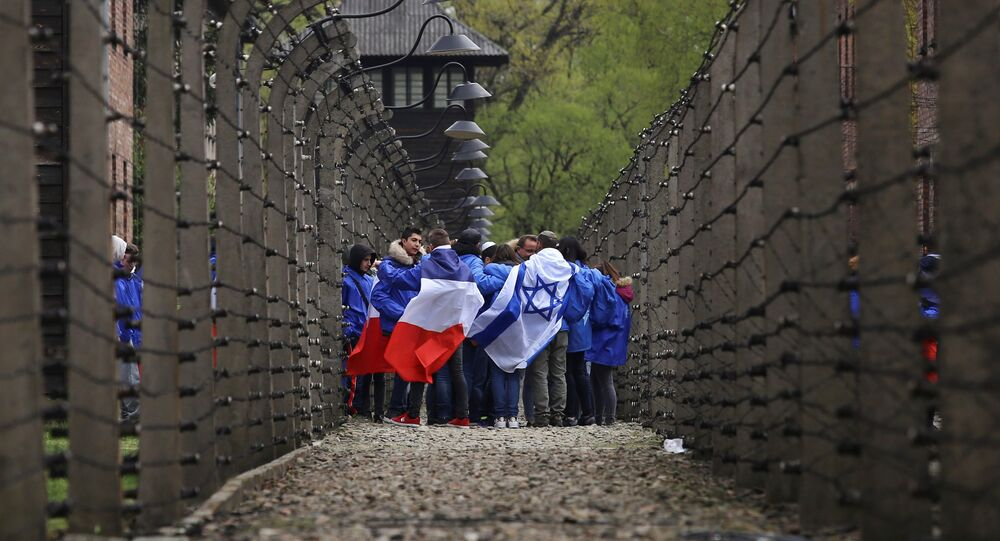 People walk between barb wire fences in the former Nazi death camp of Auschwitz as thousands of people, mostly youth from all over the world, gather for the annual March of the Living during Holocaust Remembrance Day in Oswiecim, Poland April 24, 2017.