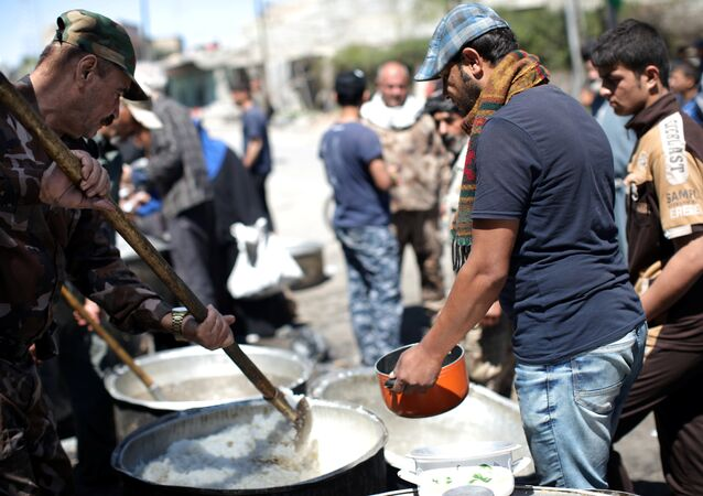 Residents receive food at a distribution point in Mosul, Iraq, April 10, 2017