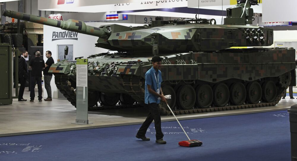 A cleaner sweeps the floor in front of a Rheinmetall MBT tank at the International Defense Exhibition and Conference, known by the acronym IDEX, in Abu Dhabi, United Arab Emirates, Sunday, 19 February 2017