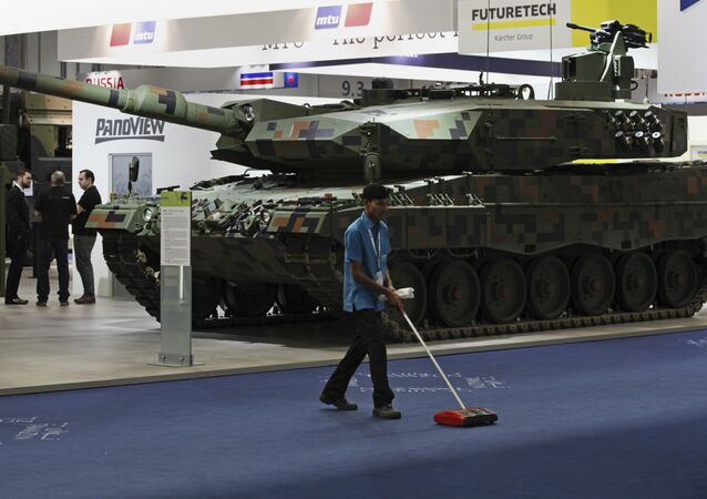 A cleaner sweeps the floor in front of a Rheinmetall MBT tank at the International Defense Exhibition and Conference, known by the acronym IDEX, in Abu Dhabi, United Arab Emirates, Sunday, Feb. 19, 2017
