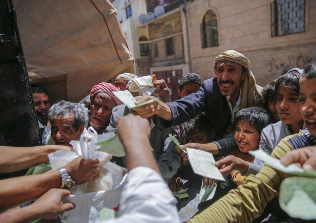 Yemenis receive food rations provided by a local charity, in Sanaa, Yemen, Thursday, April, 13, 2017.