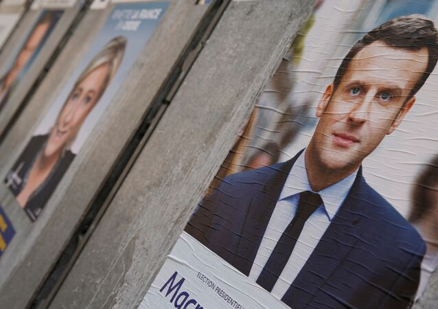 People walk past campaign posters of Emmanuel Macron (L), head of the political movement En Marche! (Onwards!), and Marine Le Pen (R), French National Front (FN) political party leader, two of the eleven candidates who run in the 2017 French presidential election, are seen in Paris, France, April 10, 2017