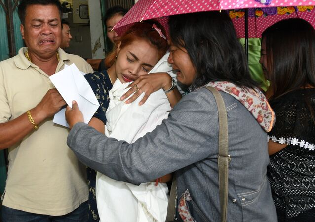 Jiranuch Trirat holds up the body of her 11-month-old daughter who was killed by her father, at a hospital in Phuket.