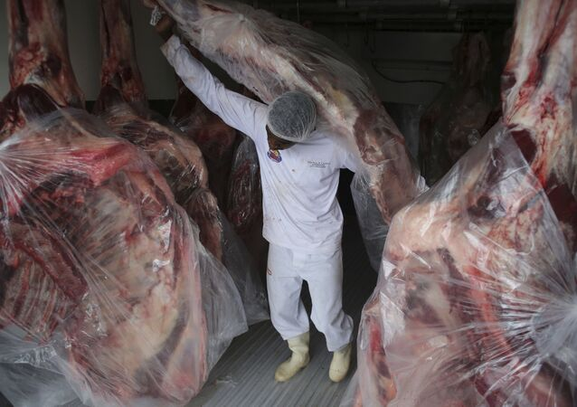 A man delivers sides of beaf to meat to a butcher shop in Brasilia, Brazil, Monday, March 20, 2017