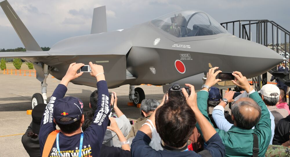 Visitors photograph a mock-up of the F-35 fighter jet displayed at the annual Self-Defense Forces Commencement of Air Review at Hyakuri Air Base, north of Tokyo, Sunday, Oct. 26, 2014