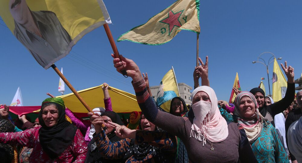 Kurdish women carry flags as they protest, in the northeastern city of Qamishli, against Turkish airstrikes on the headquarters of the Kurdish fighters from the People's Protection Units (YPG) in Mount Karachok on Tuesday, Syria April 26, 2017