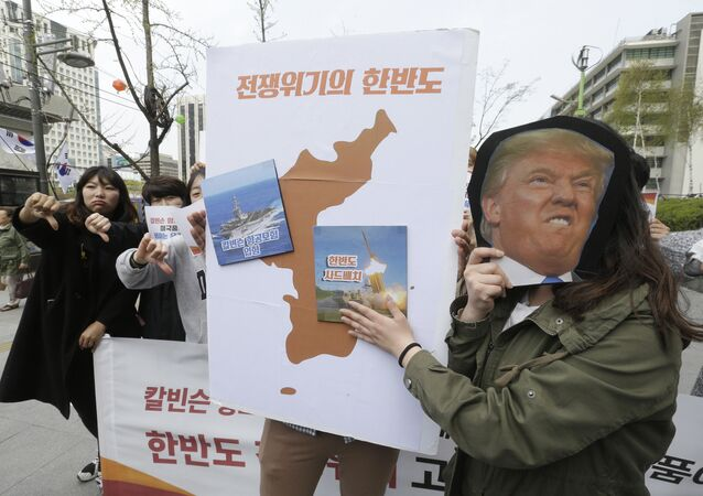 Protesters hold a cutout of US President Donald Trump and images of the USS Carl Vinson aircraft carrier and US missile defense system THAAD, right, on a map of Korean Peninsula during a rally against US deployment of the aircraft carrier to the Korean Peninsula, near the US embassy in Seoul, South Korea, Thursday, April 13, 2017