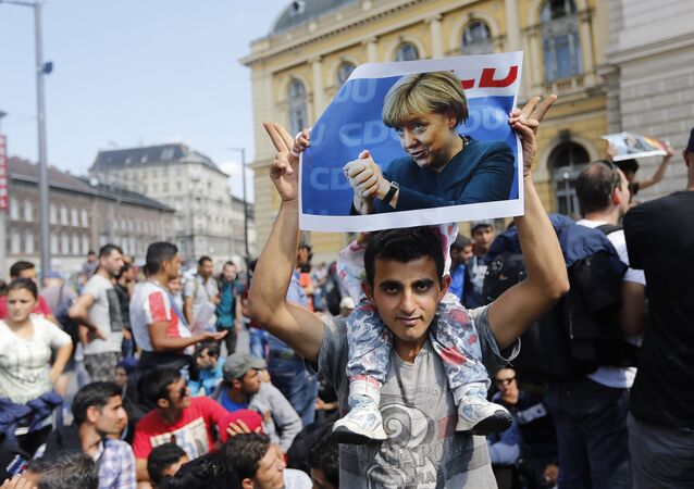 A man holds up a poster of German Chacellor Angela Merkel before starting a march out of Budapest, Hungary, Friday, Sept. 4, 2015